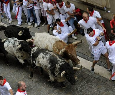Runners sprint with Torrestrella fighting bulls on Santo Domingo street during the first running of the bulls of the San Fermin festival in Pamplona